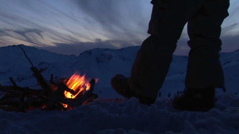 Close-up of a man's legs beside a campfire in winter Footage