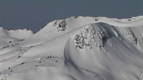 Panning-shot of deep snow covering rugged mountains Footage