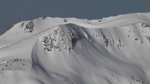Panning-shot of deep snow covering rugged mountains Stock Video Footage