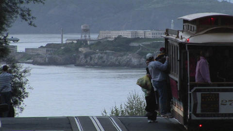 Passengers get off a trolley car on a street overlooking Alcatraz Footage