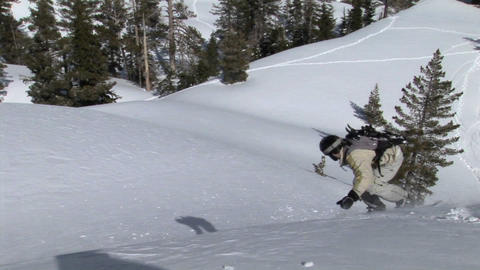 Medium-shot of a snowboarder snowboarding downhill across... Stock Video Footage