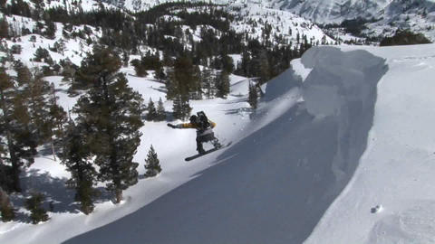 Following shot of a snowboarder jump off a slope and landing in deep powder Footage