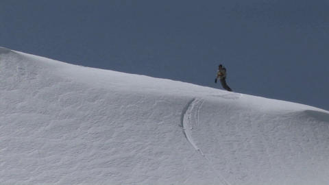 Following shot of a snowboarder as he boards slowly down... Stock Video Footage