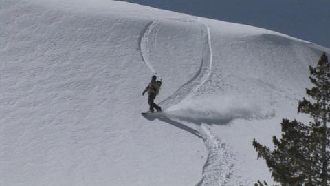 Following shot of a snowboarder as he boards slowly down a slope of virgin powder Footage
