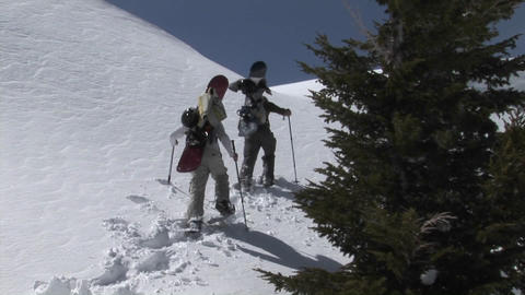 Zoom-in shot of two people on snowshoes heading up a steep and snowy slope with snowboards Footage