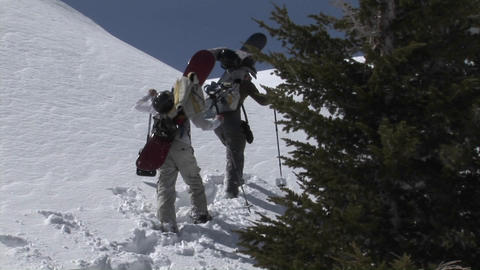 Zoom-in shot of two people on snowshoes heading up a... Stock Video Footage