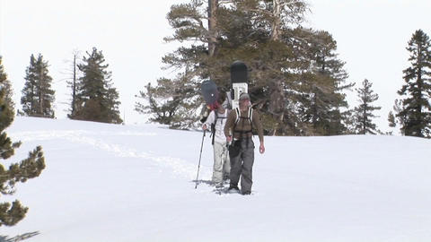Hikers snowshoe with snowboards on their backs Stock Video Footage