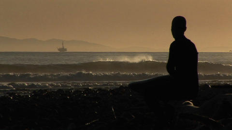 A surfer watches the waves from a beach Live Action