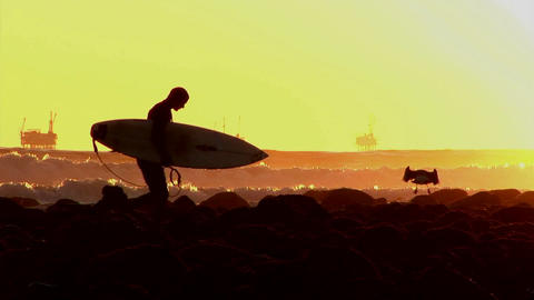 A surfer walks along the shore during golden-hour Stock Video Footage