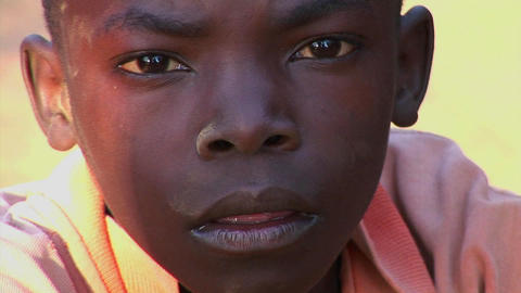 A beautiful young child stares ahead in Uganda, Africa Stock Video Footage