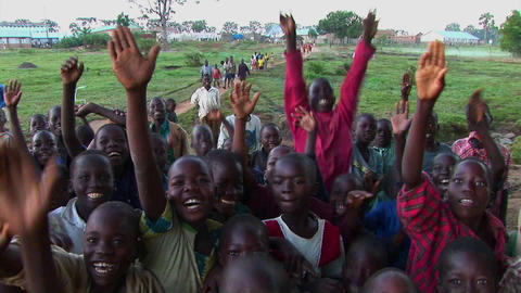 Medium shot of a crowd of children at a refugee camp Uganda, Africa, waving at the camera Footage