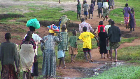 Panning-shot of a large group of children and villagers walking down a dirt path in Uganda, Africa Footage