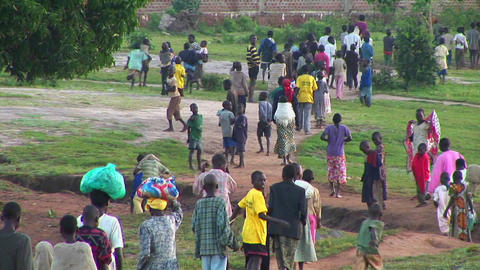 Panning-shot of a large group of children and villagers... Stock Video Footage