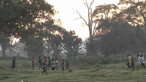 Pan-left shot of villagers walking along a path in... Stock Video Footage