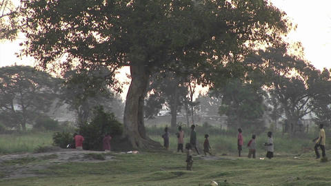 Pan-left shot of villagers walking along a path in Uganda, Africa Footage