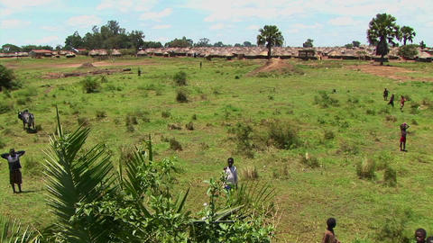 Pan-shot of open fields and a refugee camp in Northern... Stock Video Footage