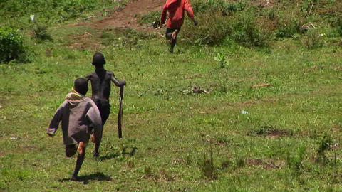 Long-shot of young children run and playing in a village... Stock Video Footage