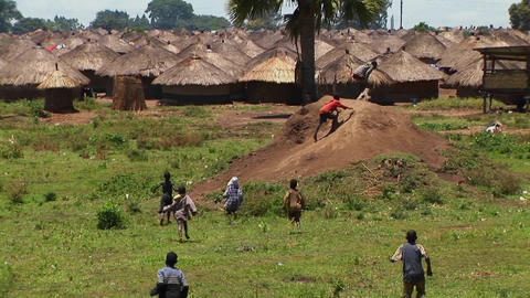 Long-shot of young children run and playing in a village or refugee camp in Northern Uganda Footage