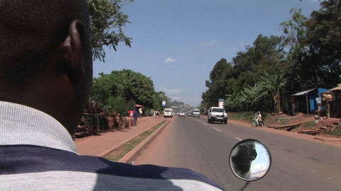 A motorcycle drives down a busy highway in Africa Stock Video Footage