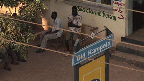 Men sit outside the Secretarial Bureau in Kampala, Uganda Stock Video Footage