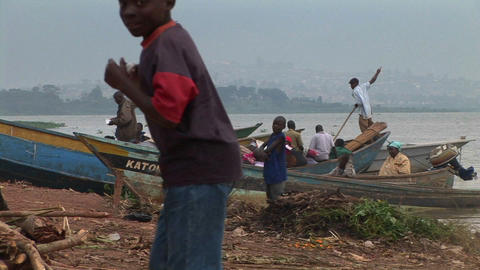 Boys standing before fishing boats at Gaba village, along the shores of Lake Victoria, Uganda Footage