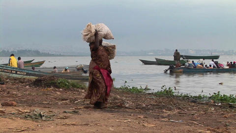 Pan-right of a heavily laden woman carrying parcels to a fishing boat on the shores of Lake Victori Footage