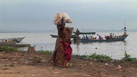 Pan-right of a heavily laden woman carrying parcels to a... Stock Video Footage