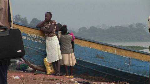 Medium-shot of a woman and children leaning against a boat on the shores of Lake Victoria Footage