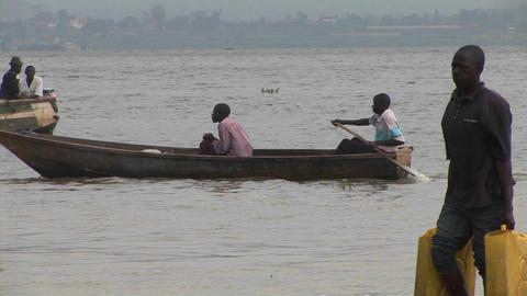 Medium-shot of a man rowing a john-boat amidst a group of other fishers on Lake Victoria, Uganda Footage