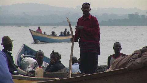 Medium-shot of a group of fishers in skiffs on Lake Victoria, Uganda Live Action