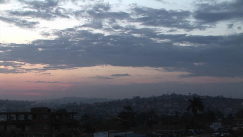 Zoom-out of a lone bird winging towards a darkening sky over Kampala, Uganda Live Action