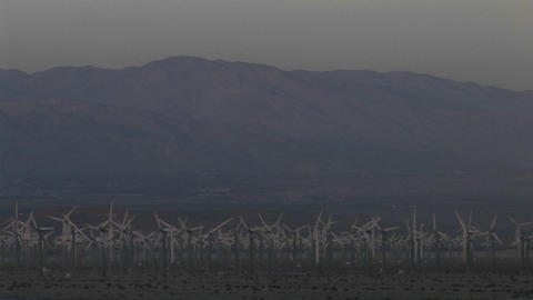 Wind turbines spin against a backdrop of mountains in the California desert Footage