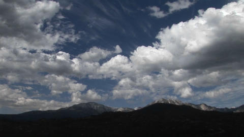 Clouds move above a desert mountain range Footage