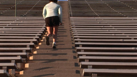Crab-left of a woman run up the steps of a large stadium Stock Video Footage