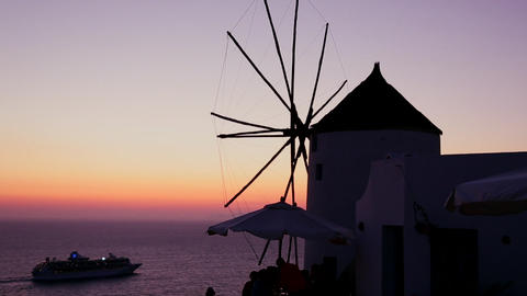 A cruise ship passes windmills at dusk or sunset o Stock Video Footage