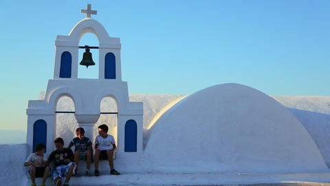 Kids sit on the white roof of a Greek Orthodox Chu Stock Video Footage