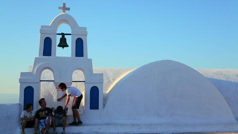 Kids sit on the white roof of a Greek Orthodox Chu Footage