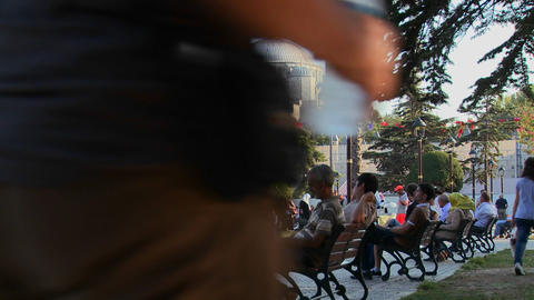 Pedestrians walk and sit on benches near the Blue Stock Video Footage