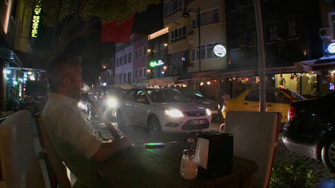 A man sits near a busy street at night and smokes Stock Video Footage