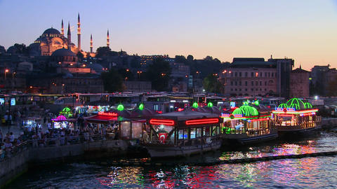 Colorful boats at dusk in front of a mosque in Ist Stock Video Footage
