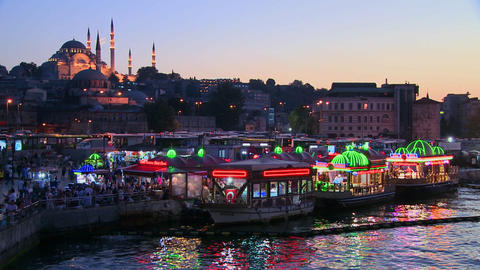 Colorful boats at dusk in front of a mosque in Ist Footage