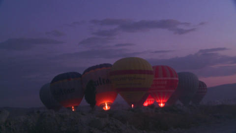 Hot air balloons firing up at dawn Stock Video Footage