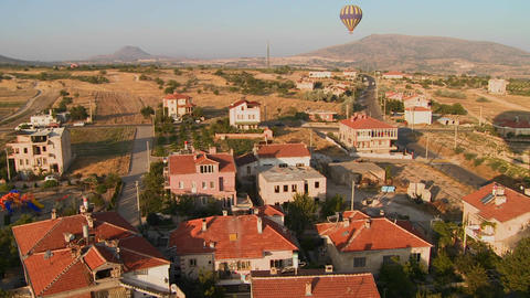 Hot air balloons fly over a neighborhood near Capp Stock Video Footage