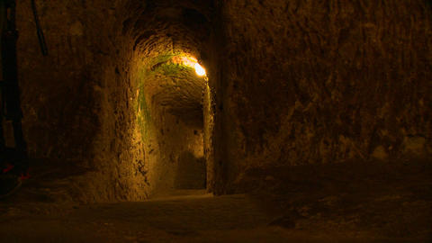 A woman walks in a tunnel or cave in an undergroun Stock Video Footage