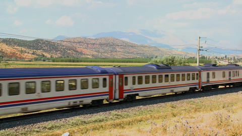 A passenger train travels across a generic landsca Footage