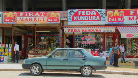 Car is parked in front of colorful shops and signs Stock Video Footage