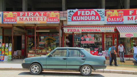 Car is parked in front of colorful shops and signs Footage