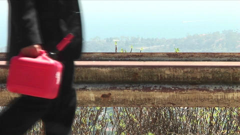 A man walks down a road with a bright red gas can Stock Video Footage