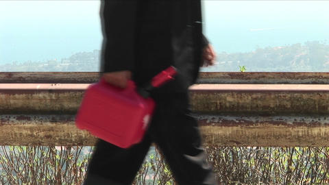A man walks down a road with a bright red gas can Footage