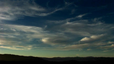 Thin, wispy clouds drift across a blue green sky Footage